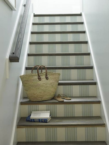 Une déco douce et apaisante dans les escaliers de la maison aux murs blancs avec du papier peint beige et vert pastel à motifs posé sur les contremarches !