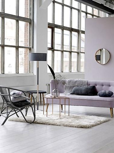 Voilà un salon couleur pastel plein de douceur ! Couleur parme, parquet blanc, tapis, et mobilier tendance assure une déco cosy soulignée par un fauteuil en rotin noir