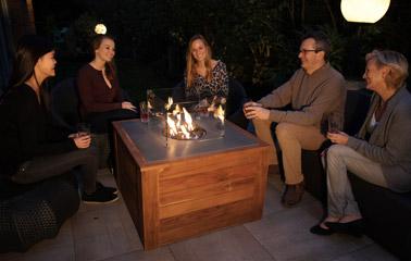 Les soirées se font douces à l'extérieur tout au long de l'année grâce à une table basse ingénieuse dotée d'un foyer central pour une ambiance chaleureuse et festive