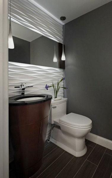 On mise sur une déco design dans la salle de bain avec un mariage de blanc et de gris anthracite mis en valeur par deux suspensions lumineuses ultra chic