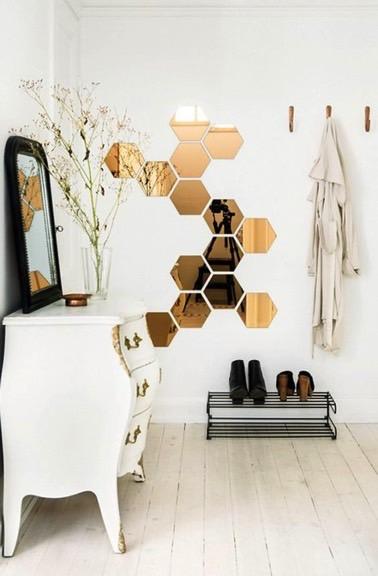 Voilà une bonne idée pour habiller le hall d'entrée ! Des miroirs de formes hexagonales placés sur le mur donnent du style à ce petit espace accueillant