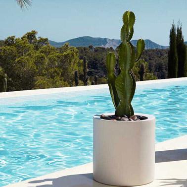 On opte pour un pot de forme cylindrique pour décorer la piscine avec classe ! De couleur blanc, il accueille un cactus et des galets pour un effet déco top