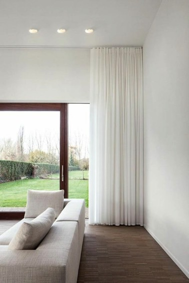 Avec des rideaux blancs placés juste devant la grande baie vitrée donnant sur le jardin dans ce salon moderne avec parquet, on ne peut pas se tromper !