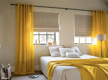 Dans cette chambre beige, la déco est dynamisée grâce aux rideaux jaunes qui donnent du peps à la pièce et font un clin d'oeil au plaid de la même couleur !