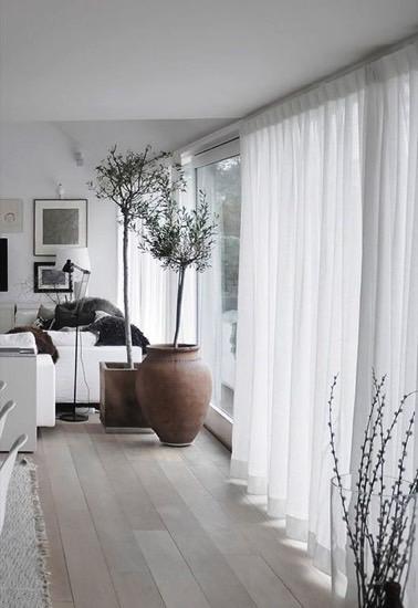La déco scandinave de ce salon mise sur des rideaux blancs style voilages afin de faire entrer la luminosité et d'apporter une touche de douceur et de pureté