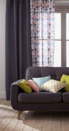 La déco simple et sobre de ce salon avec parquet est dynamisé par un rideau gris accompagné d'un joli voilage pastel à motifs faisant écho aux coussins colorés