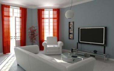 Dans ce salon design aux murs gris perle et au mobilier blanc, la luminosité traverse la pièce grâce à des rideaux de type voilages de couleur rouge très élégants