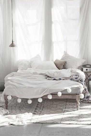 On craque pour le style bohème de cette chambre aux tons naturels où la déco est joliment soulignée par des voilages blancs, un lit en bois et un beau tapis