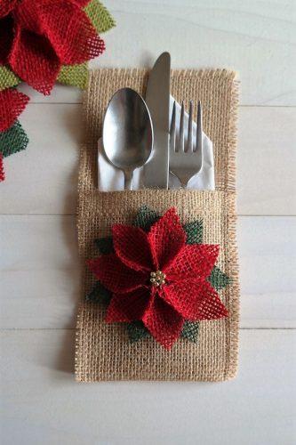 Pour créer votre propre pochette à couverts personnalisée, prenez une pièce de tissu de 25x10cm, puis rabattez un tiers de la longueur et cousez les bords pour former une pochette. Décorez-la avec des perles, des paillettes, du tissu ou même de petites peluches de Noël!