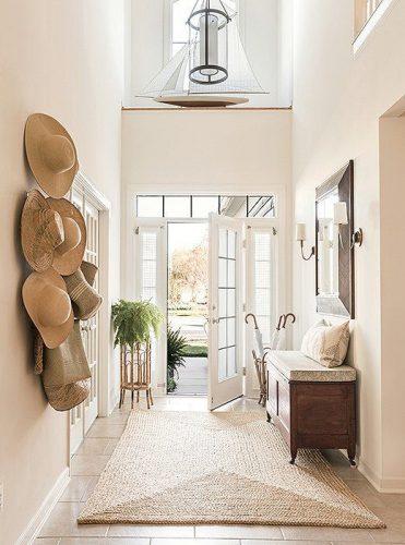 Tapis naturel en sisal, dans l'entrée d'une maison au coloris très pastel.