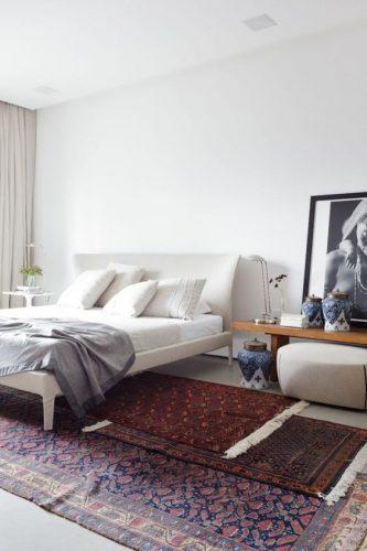 Superposition de plusieurs tapis persans dans une chambre pour une descente de lit raffinée.