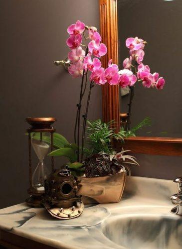 L'orchidée apporte une décoration délicate et harmonieuse sur un rebord de lavabo.