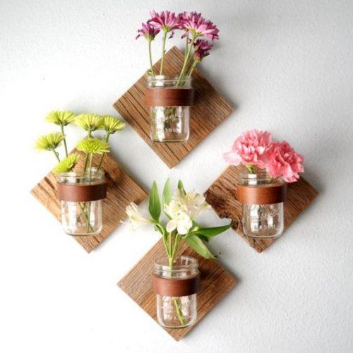 Pots de confiture utilisés comme pots de fleurs sur leurs supports muraux