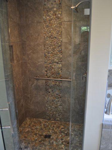 Plaques de galets au sol et au mur d'une douche italienne