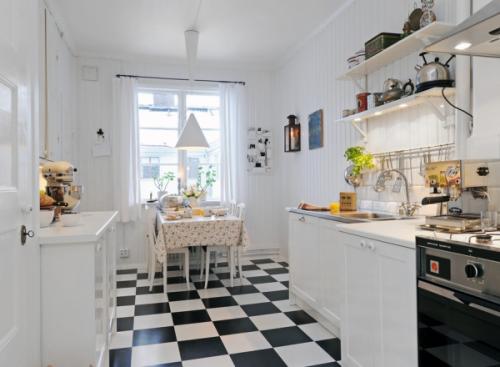 Une cuisine toute blanche en contraste avec un sol à damier