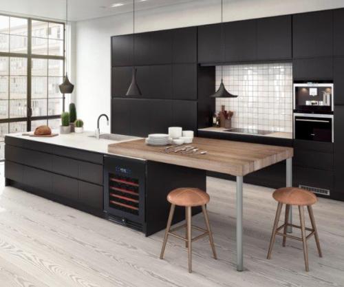 meubles de cuisine peints en noir en contraste avec un plan de travail et une crédences blancs et une table bar en bois